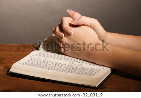 Hands folded in prayer over open russian Holy Bible on black background