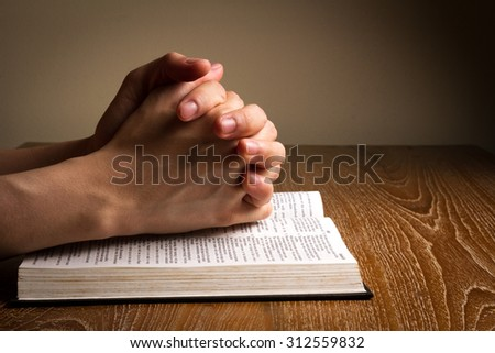 hands folded praying on bible