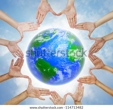 Hands forming  a circle with planet Earth in center and sky background - stock photo