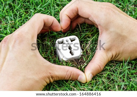 hands forming a heart shape around a socket / clean energy / green energy / save the world - stock photo