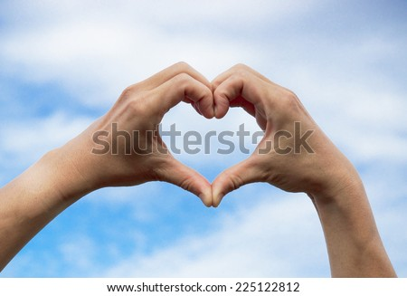 hands forming a heart shape with sky and cloud