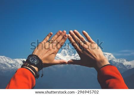 Hands framing the snowy mountain peak. - stock photo