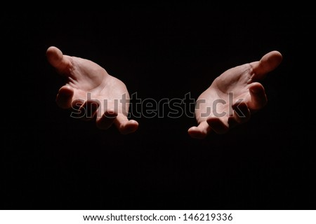 Hands from the dark. Close-up of human hands stretching out from the dark - stock photo