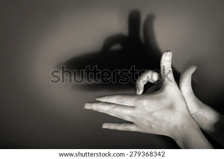 Hands gesture like dog face on gray background - stock photo