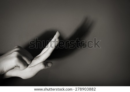 Hands gesture like snail on gray background