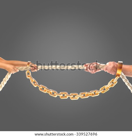 Hands girls and adult men pulling the rope in gold chains on black background.   - stock photo