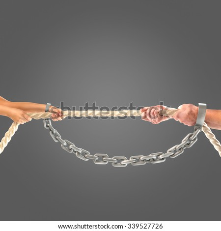 Hands girls and adult men pulling the rope in iron gold chains on black background.