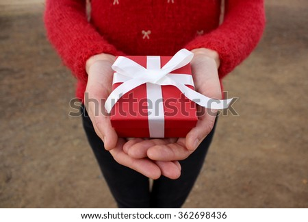 Hands giving a red present - stock photo