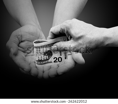 hands giving twenty dollars bank note isolated on black with path - stock photo