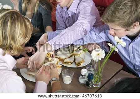 Hands grabbing sandwiches from plates in a restaurant - stock photo