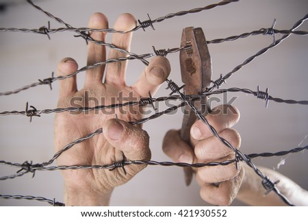 Hands gripping the barbed wire in the sign to run away with the white background - stock photo