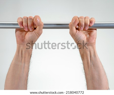 Hands hanging a metallic bar.perseverance concept. - stock photo
