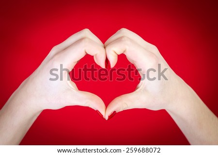 Hands heart isolated on red background - stock photo