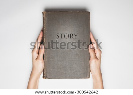 "hands hold the  book with a word of "" Story "" on cover - stock photo"