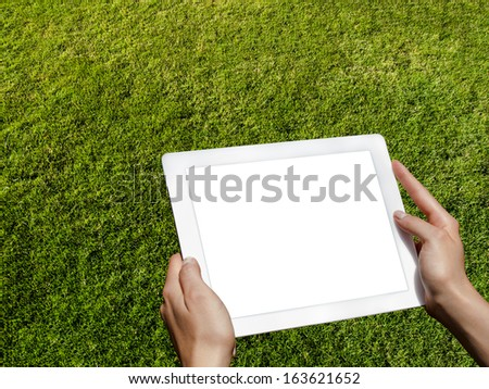 hands hold the tablet on a background of grass - stock photo