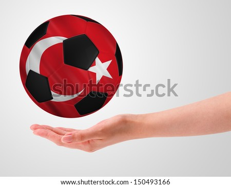 Hands holding a ball with flag of turkey - stock photo