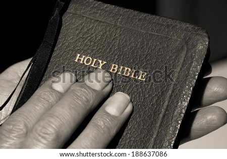 Hands holding a bible - slight sepia tone - stock photo