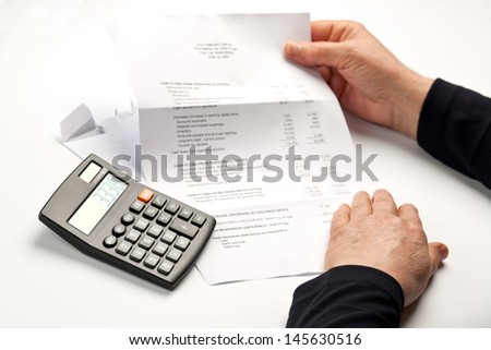 Hands holding a bill or a financial statement next to a calculator. Focus on the calculator. - stock photo