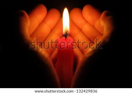hands holding a burning candle in dark like a heart - stock photo