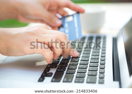 Hands holding a credit card and using laptop computer for online shopping