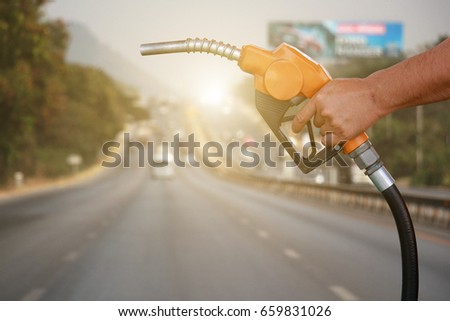 Hands holding a fuel nozzle on cars and land transport on the street is the background.