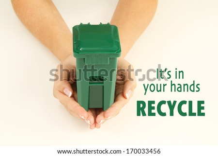 Hands holding a garbage can. It's in your hands, recycle.  - stock photo