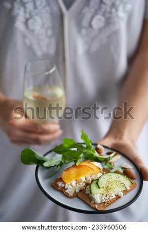 Hands holding a glass of wine and a plate of fresh cheese canapes topped with nectarine and cucumber at a party - stock photo