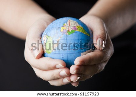 hands holding a globe isolated on black
