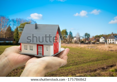 Hands holding a house model against building ground background - stock photo