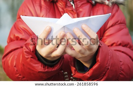 hands holding a paper boat closeup - stock photo