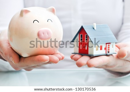 Hands holding a  piggy bank and a house model. Housing industry mortgage plan and residential tax saving strategy - stock photo
