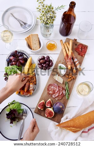 Hands holding a plate and reaching out for cheese and cured meat charcuterie selection salami, chorizo, parma ham wrapped bread sticks with fresh fig, rockmelon, almonds and white wine - stock photo