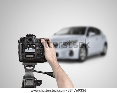 Hands holding a professional camera on tripod taking picture of a car in studio. grey gradient background. - stock photo