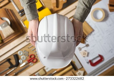 Hands holding a protective safety helmet against a work table with hardware and construction tools, top view - stock photo