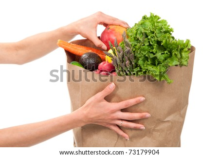 Hands holding a shopping paper bag full of groceries, one hand pick out ripe mango, avocado, asparagus, carrots, radish, lime and lemon on a white background - stock photo