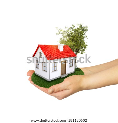 Hands holding a small house with land. Isolated on white background