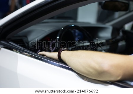 Hands holding a steering wheel of the modern car. Focus on hands - stock photo