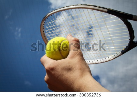 Hands holding a tennis ball and a racket against a half blue, half cloudy sky