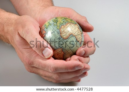 Hands holding a vintage globe as if protecting it