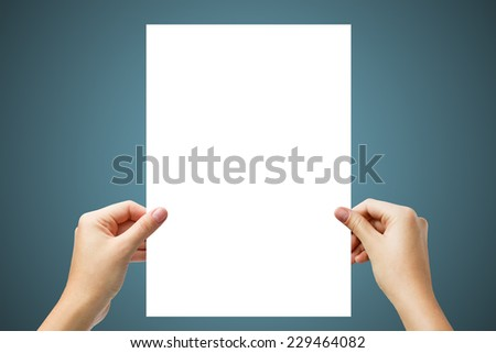 Hands holding a white paper blank isolated on light blue background  - stock photo