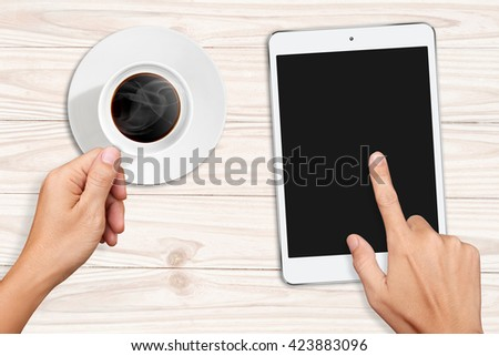 Hands holding acup of coffee and Touch on Small White Tablet Computer on white wooden table - stock photo