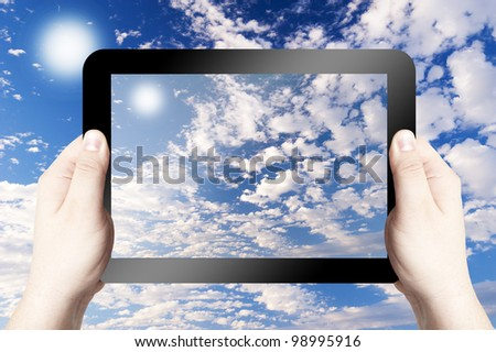 Hands holding and point on digital tablet. Tablet PC with blue sky on the screen. - stock photo