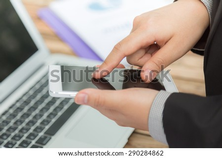 Hands holding and pointing on Smart Phone - stock photo