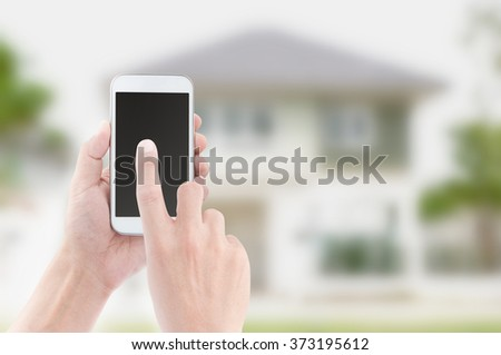 Hands holding and touch screen of smart phone on house backgrounds - stock photo