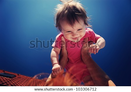 Hands holding baby up and blue sky - stock photo