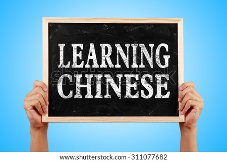 Hands holding blackboard with text Learning Chinese against blue background.
