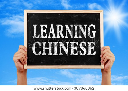 Hands holding blackboard with text Learning Chinese against blue sky background.