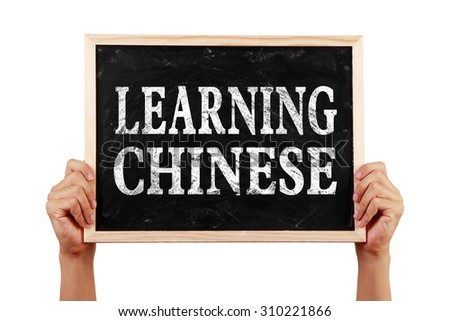 Hands holding blackboard with text Learning Chinese isolated on white background.