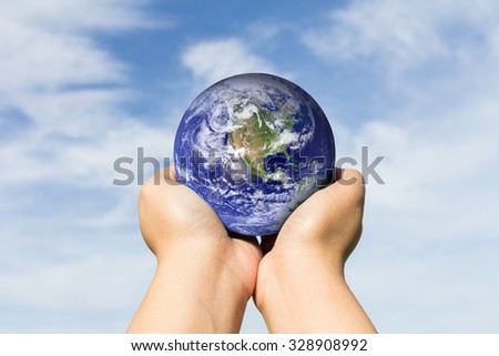 hands holding blue earth on cloud and sky background. Elements of this image furnished by NASA