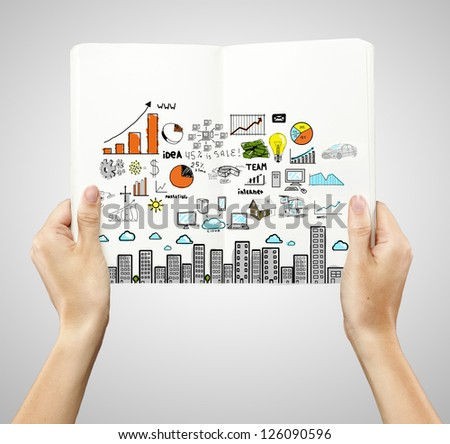 hands holding book with drawing colorized city - stock photo